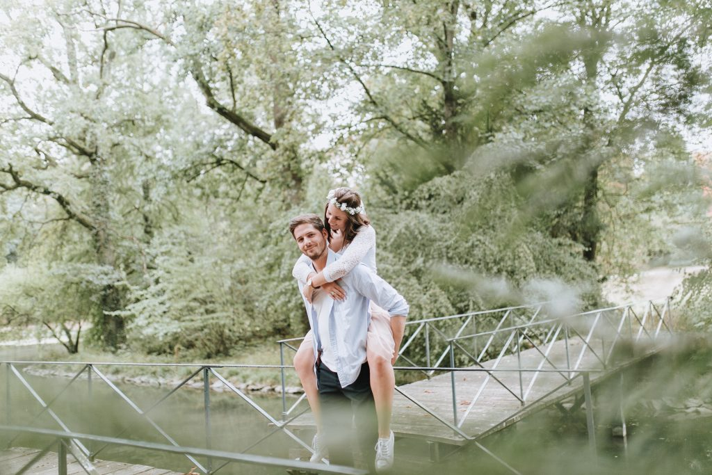 Pärchen auf einem Steg am See in Aschaffenburg. Mann trägt Frau.