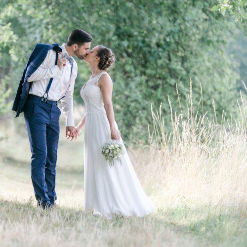 Brautpaar im Wald küsst sich